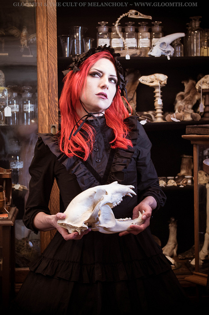 red hair gothic model holding a bobcat skull in an antique shop