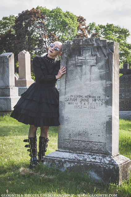 bald gothic woman leans against tombstone