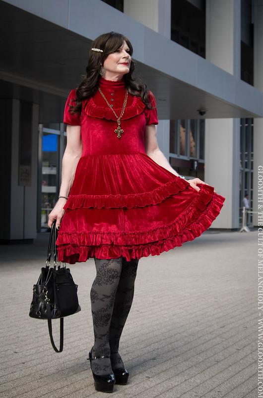 drag queen in red velvet gothic dress