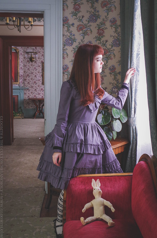 classic lolita looking out a window of a victorian home