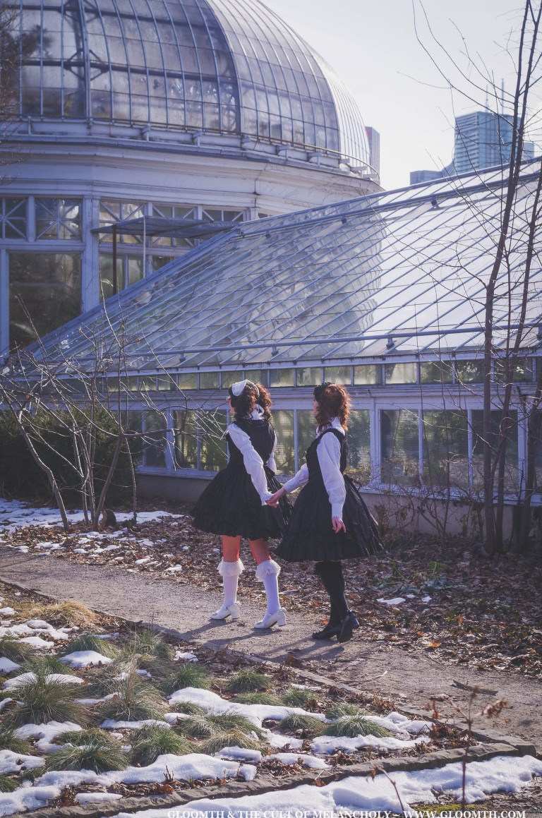 two gothic lolitas walking towards a greenhouse